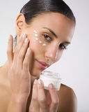 Woman applying lotion. A studio portrait of a beautiful young woman applying moisturizing lotion Stock Images