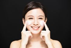 Woman applying lotion cream on face. Happy woman applying lotion cream on face royalty free stock photography