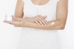 Woman applying lotion on her hands Royalty Free Stock Photos