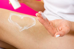 Woman applying lotion on her leg Stock Photography