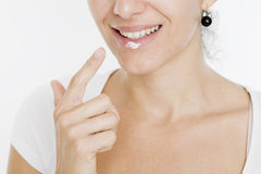 Woman applying lotion on her lips Stock Photography