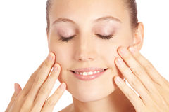 Woman applying lotion to her face Stock Photography
