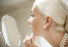 Woman applying make-up Royalty Free Stock Images