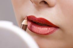 Woman applying make up Royalty Free Stock Image