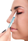 Woman applying make-up Stock Images