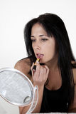 Woman applying make-up. In a small mirror Stock Images