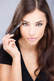Woman applying make up. Pretty black hair woman applying make up with brush in her right hand stock images