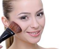 Woman applying make-up Stock Photo
