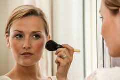Woman Applying Make-up, looking in a mirror Stock Photography