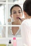 Woman applying make-up Royalty Free Stock Photos