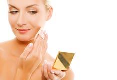 Woman applying make-up Stock Photography