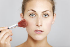 Woman applying make up Stock Images