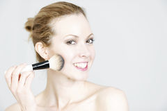 Woman applying make up stock image
