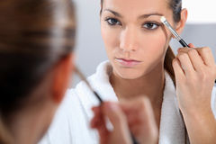 Woman applying make-up Stock Photo