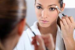 Woman applying make-up. In bathroom Stock Photo