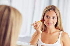 Woman applying make up with a big brush and looking in the mirror stock photo