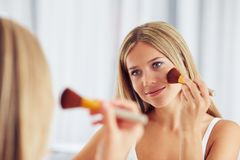 Woman applying make up with a big brush and looking in the mirror stock images