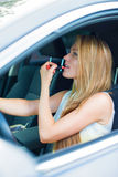 Woman applying make-up while driving car. Stock Images