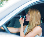Woman applying make-up while driving car. Royalty Free Stock Photography