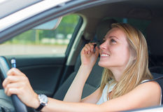 Woman applying make-up while driving car. Stock Photo