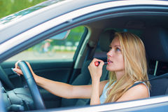 Woman applying make-up while driving car. Stock Photography