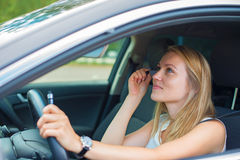 Woman applying make-up while driving car. Royalty Free Stock Image