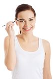 Woman applying make up on her eyebrow Royalty Free Stock Images