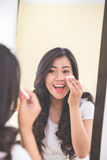 Woman applying make up into her face Stock Images