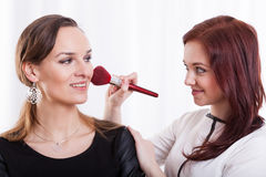 Woman applying make up for her friend Stock Photo