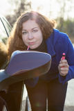 Woman applying make up near car back side mirror Stock Image