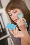 Woman applying make up in office Stock Photos