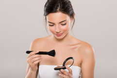 Woman applying make up Royalty Free Stock Images