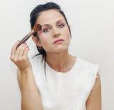 Woman applying make up Stock Photography