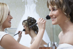 Woman Applying Make-up To Bride's Face Royalty Free Stock Images