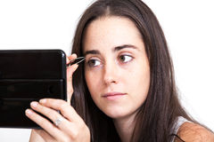 Woman applying make-up. Young woman applying make-up Stock Images