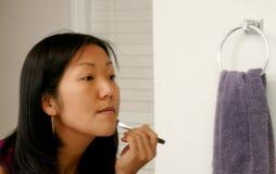 Woman Applying Makeup Stock Image