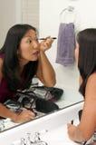 Woman Applying Makeup Stock Photography