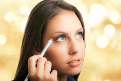Woman applying makeup Royalty Free Stock Image