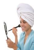 Woman applying makeup Stock Images