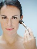 Woman applying makeup with brush Royalty Free Stock Photo