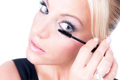Woman applying makeup with brush on eye-lash Stock Photo