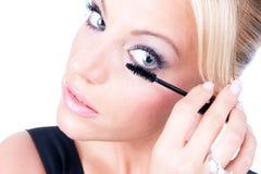 Woman applying makeup with brush on eye-lash stock photo