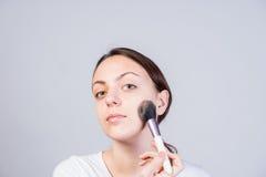 Woman Applying Makeup on Cheek Using Brush Royalty Free Stock Photo