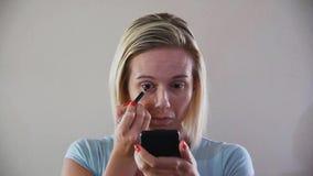 Woman applying makeup stock video