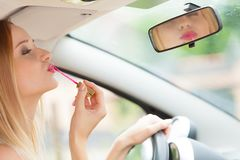 Woman applying makeup while driving her car Royalty Free Stock Photography