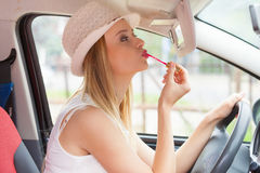 Woman applying makeup while driving her car Stock Photo