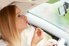 Woman applying makeup while driving her car Royalty Free Stock Photo