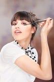 Woman applying makeup on eyelash. Woman doing cosmetic treatmant on eyelash Royalty Free Stock Photography