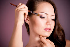 Woman applying makeup on face Royalty Free Stock Images