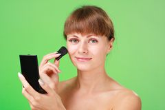 Woman applying makeup on a green background Royalty Free Stock Photography
